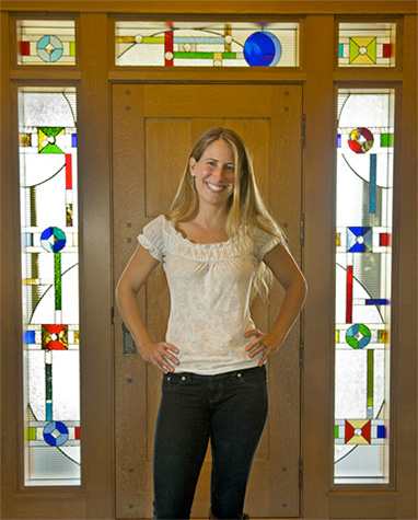 Amy Boughton stands in front of her stained glass door for a client.